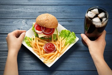 Woman with burger, french fries and cola on wooden background