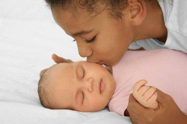 Girl kissing her little sister, closeup