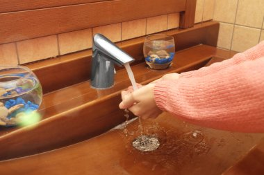 Young woman washing hands in sink, close up view