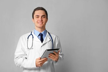 Young male doctor with tablet on grey wall background