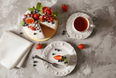 Piece of delicious cake with berries on grey table, top view