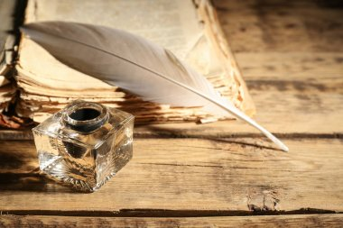 Feather pen with inkwell and stack of papers