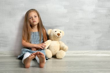 Cute little girl with teddy bear sitting