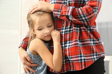 Mother hugging cute little girl