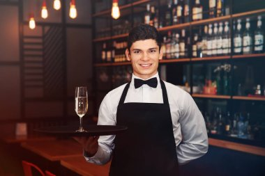 Male waiter holding tray with champagne