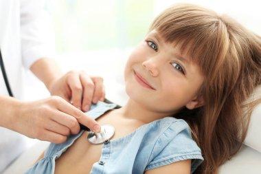 Pediatrician examining little girl