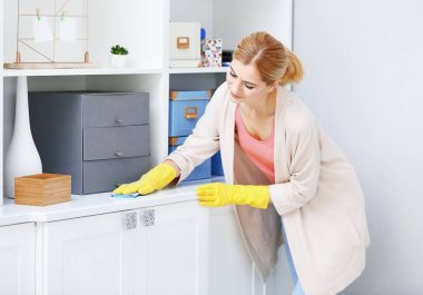 woman wiping furniture at home