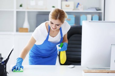 woman wiping table in office