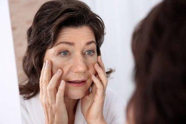 Senior woman touching face