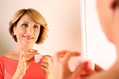 senior woman looking in mirror