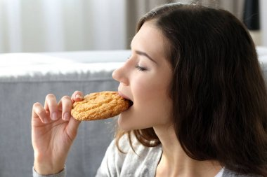 Woman eating tasty cookie