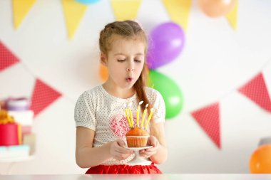 Cute little girl blowing out candles