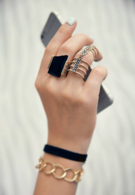 hand with jewelry and cellphone