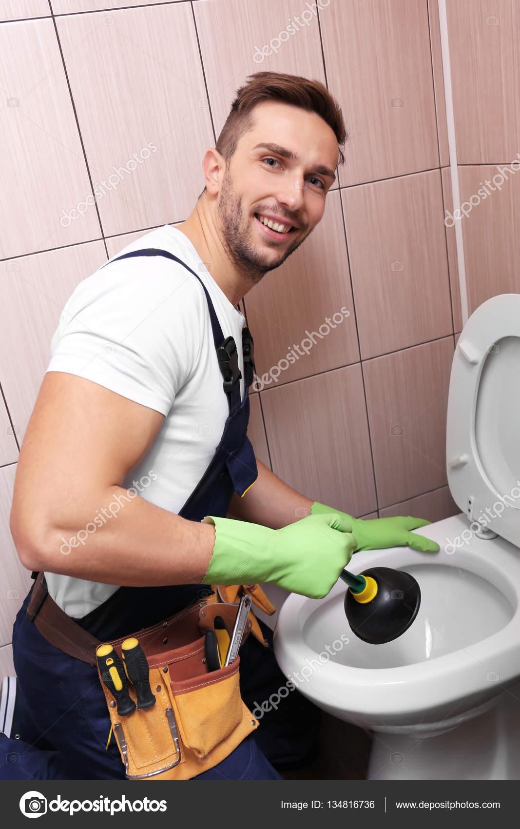 Plumber repairing toilet — Stock Photo © belchonock #134816736