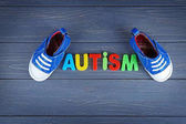 Fotografie Word AUTISM with kids shoes