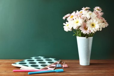 Copybooks and flowers on desk