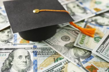 graduation hat on dollar banknotes.