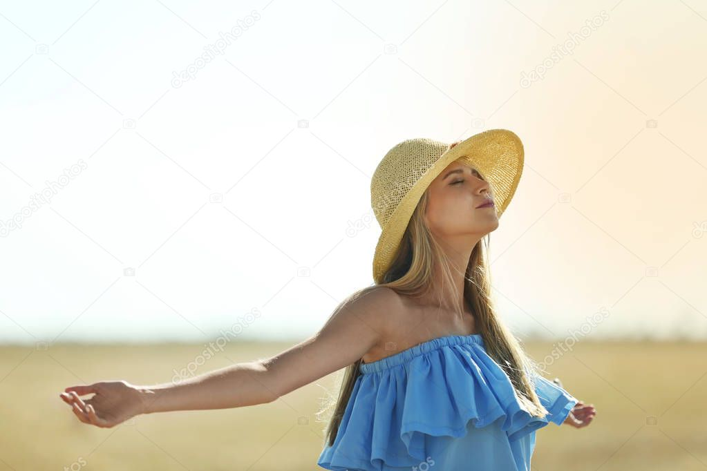 Young woman in field on blue sky background