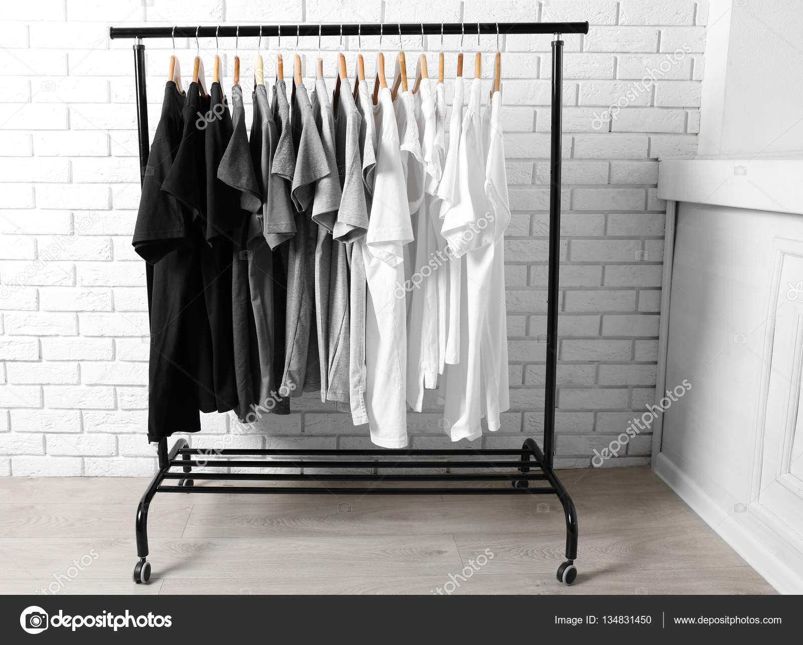T-shirts on hangers against brick wall — Stock Photo