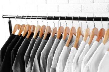 t-shirts on hangers against brick wall