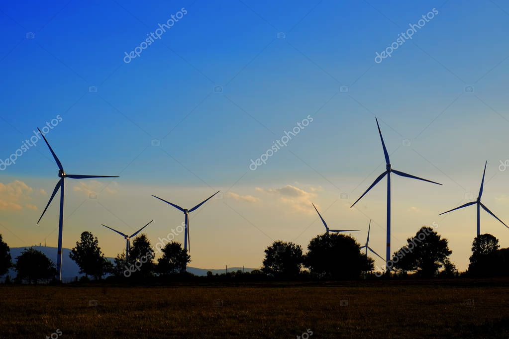 Windmills on field at sunset