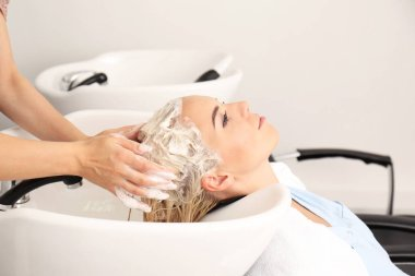 Hairdresser washing woman's hair