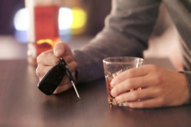 Man sitting in bar with car key and glass