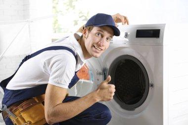 Plumber repairing washing machine