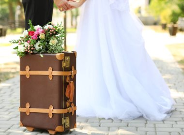 Vintage suitcase and groom with bride