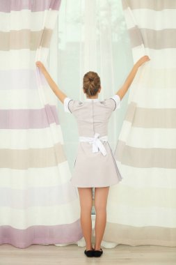 Chambermaid adjusting curtains in the room