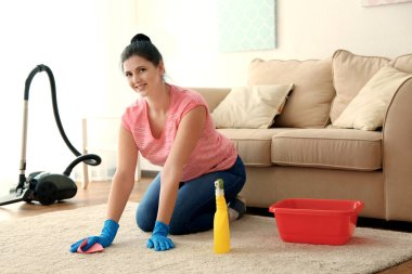 Woman cleaning carpet in room