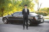 Chauffeur steht neben Luxusauto