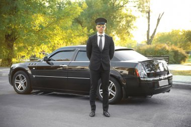 chauffeur standing near luxury car