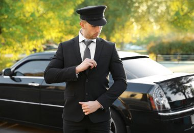 Young chauffeur adjusting suit