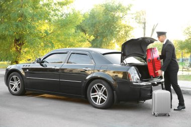 Chauffeur putting suitcase