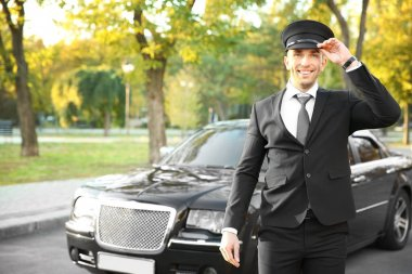 Young chauffeur adjusting hat