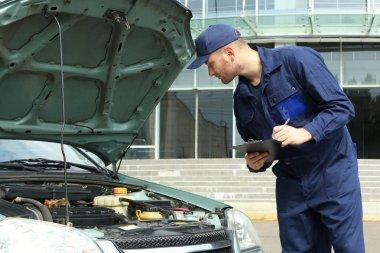 Mechanic in front of open car