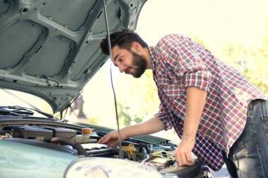 man looking under car hood