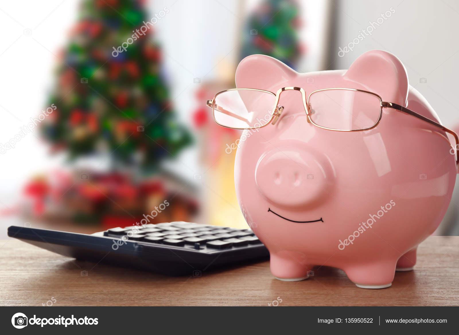 De concept van de kosten van de vakantie piggy bank met bril op