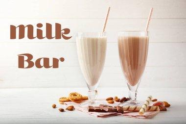 Glasses of tasty milk shakes on table