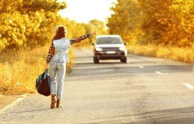 Young woman with backpack hitchhiking on road