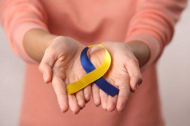 female hands holding  ribbon.