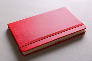 Red notebook on light surface
