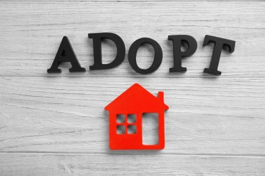 Word ADOPT and figure in shape of house