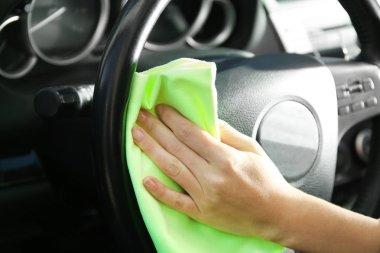 Man wiping interior of car