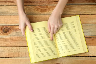 Female hands holding opened book