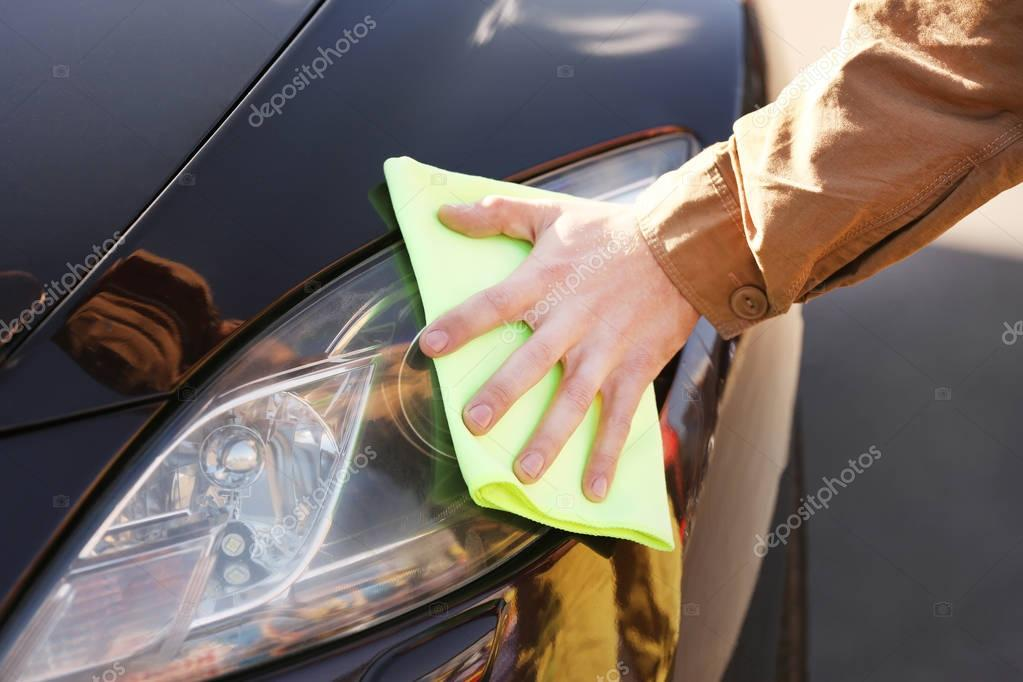 Male hand wiping headlights of car