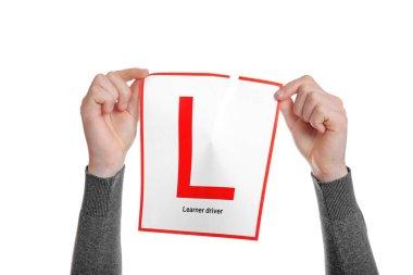 man tearing learner driver sign