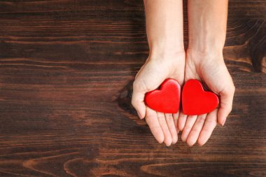 Female hands holding red hearts