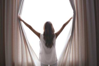 Beautiful woman opening curtains